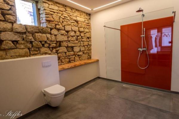 Traum-Bad mit alter, beleuchteter Steinwand
